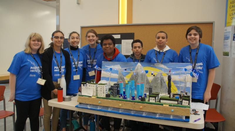 Four male and four female students with their future city model