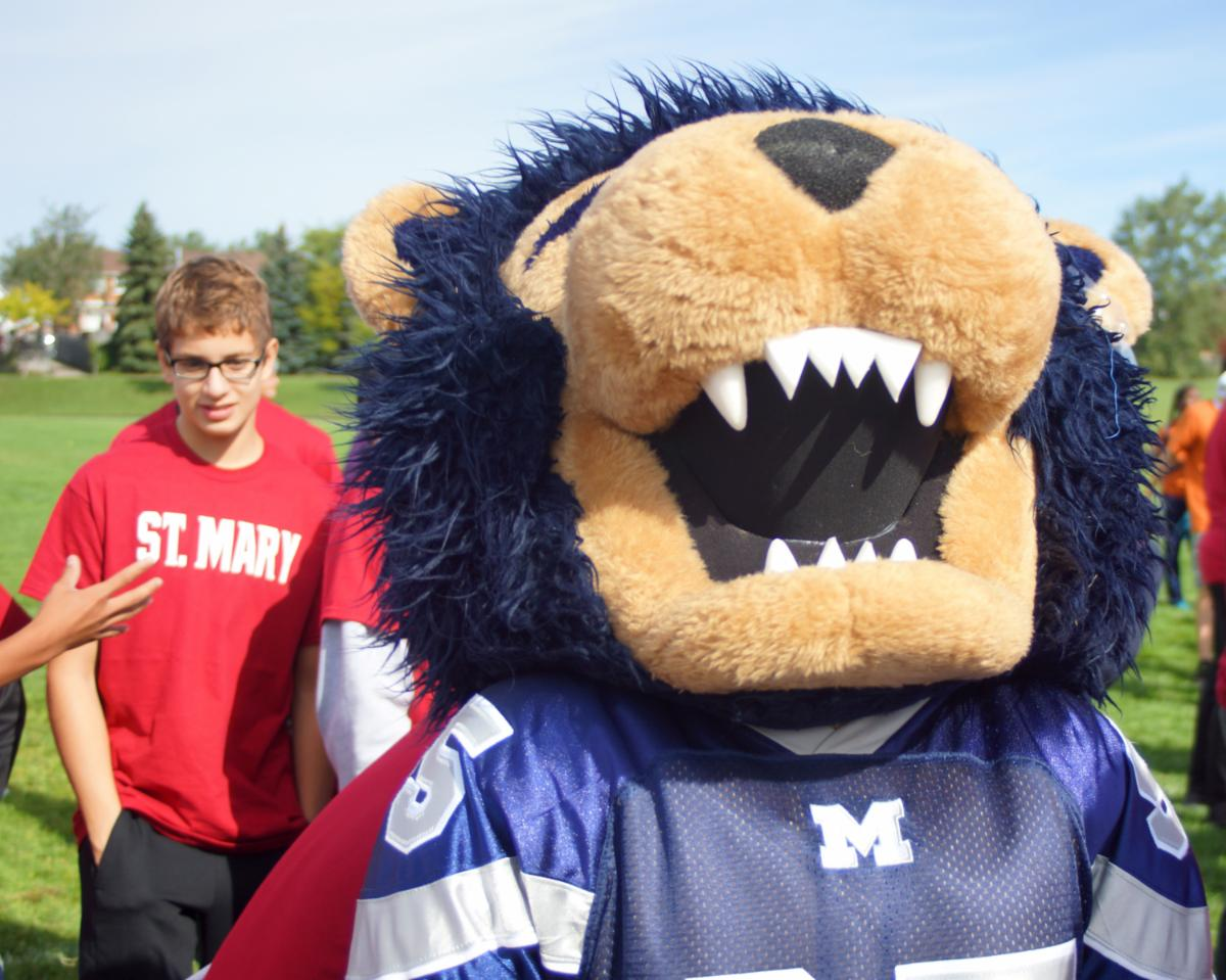 School mascot wearing a St. Mary jersey outside with students