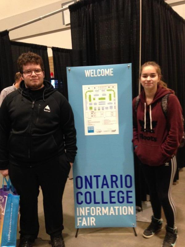 Male and female student standing beside the Ontario College Information Fair banner