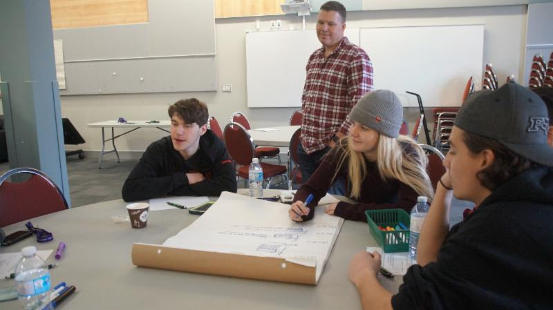 Male adult listens to students brainstorm ideas on challenge