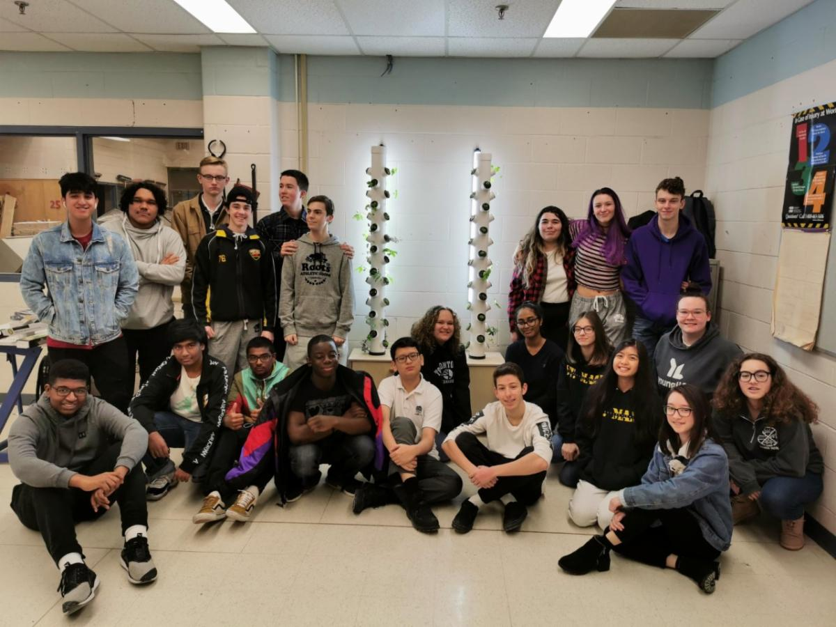 A group of male and female Green Industries students standing and sitting around the aeroponic gardening system.