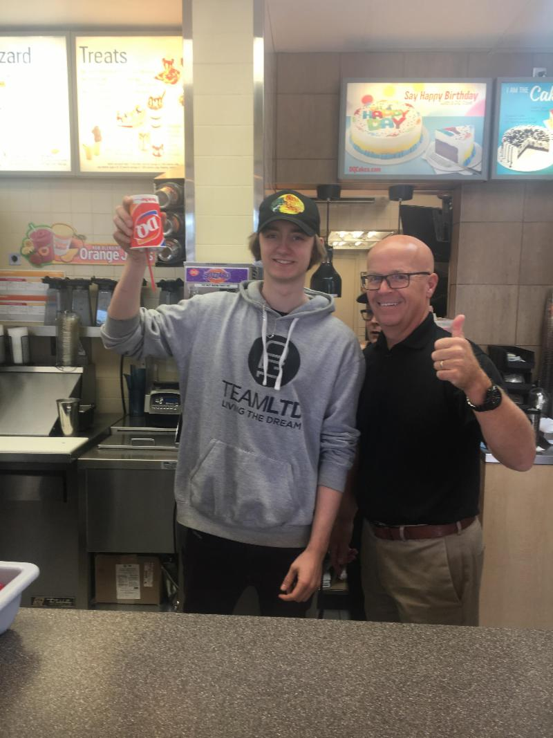 Male student holding a blizzard upside down and owner giving the thumbs up