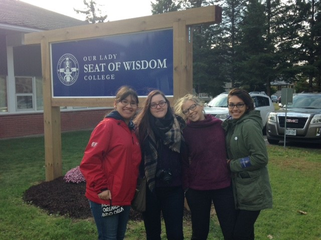 Four female students pose for picture by the Our Lady Seat of Widsom sign