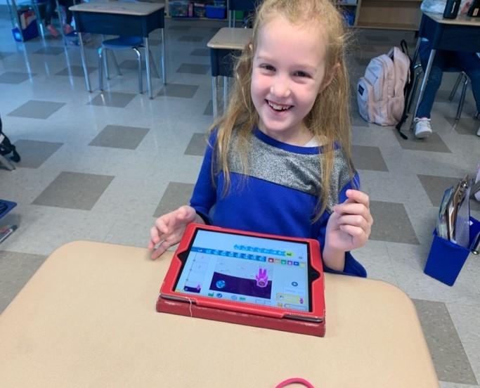 Female student coding on an iPad