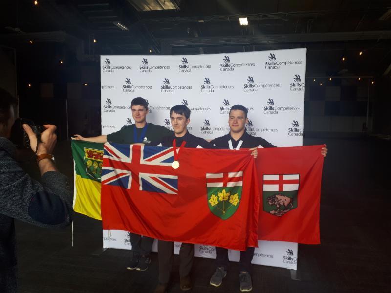 Three male students holding flags and wearing their medals
