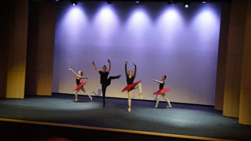 Three female and one male dancer performing on stage