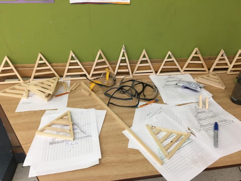 Wooden triangles built by students displayed on a table.