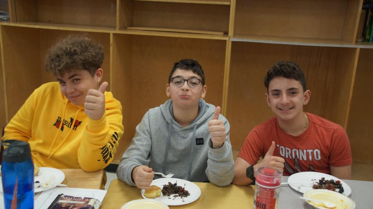 Three male students giving thumbs up to the Indigenous inspired meal.