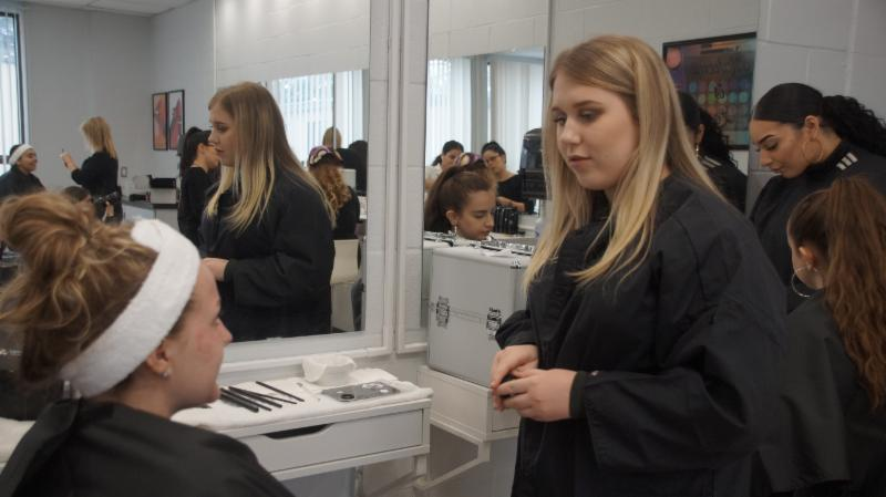 Female student artists communicating with her client before apply makeup