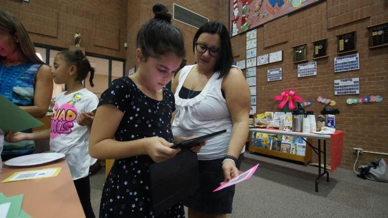 Female student scans a code using an iPad and app to facilitate learning.