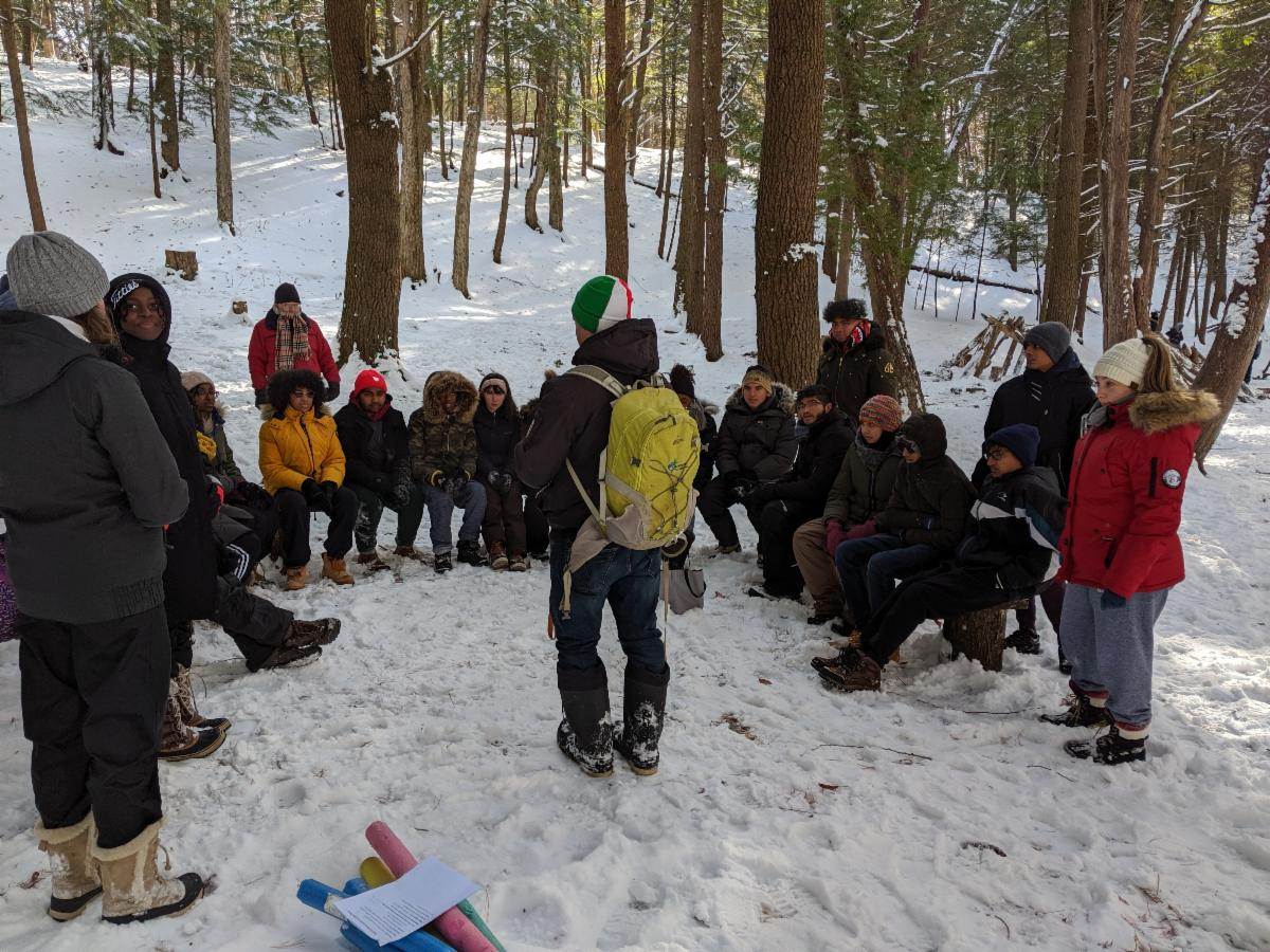 A group of students outside in the forest and snow.