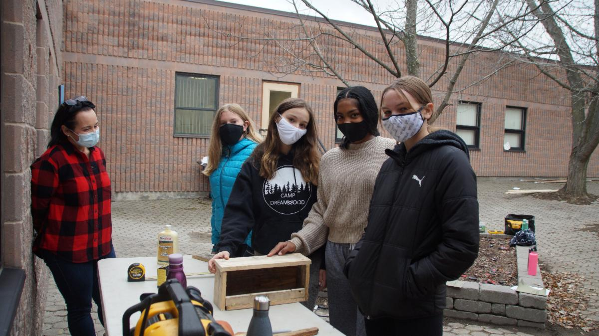 Five female students building bird houses