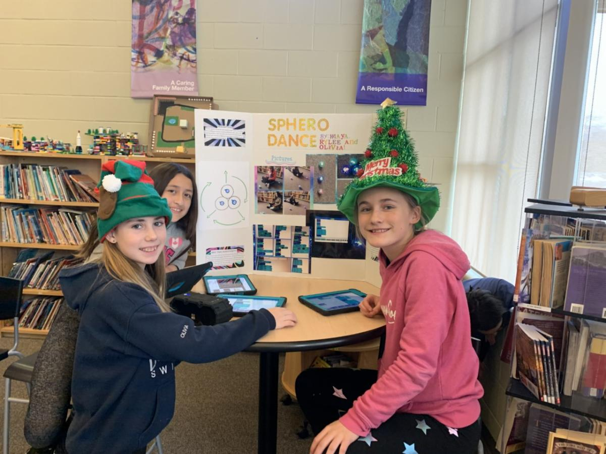 Three female students demonstrate their coding skills