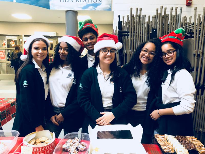 Students wearing Christmas hats selling items during a bake sale