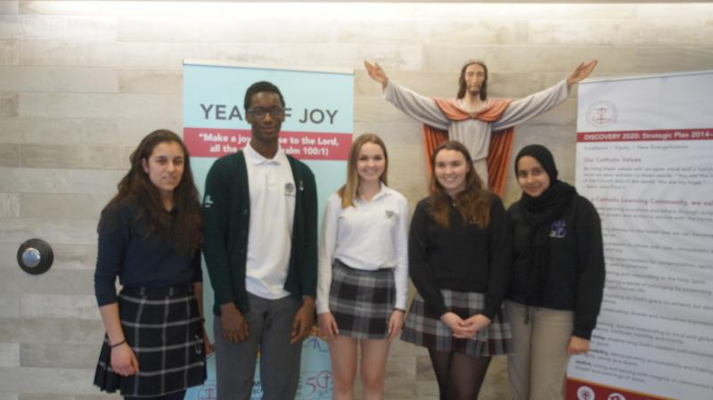 Four female students with one male student with statue of Jesus in the background.