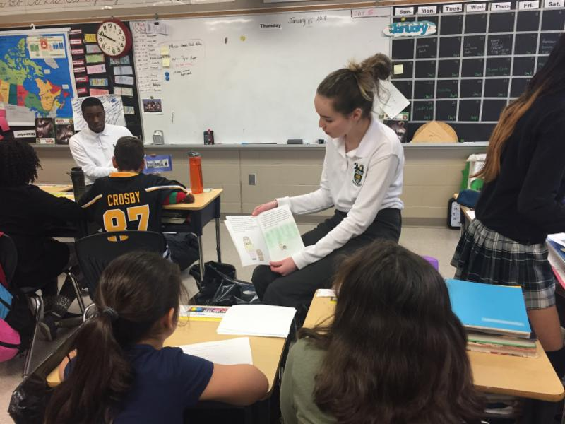Female secondary student reads her story to the elementary students in a classromm