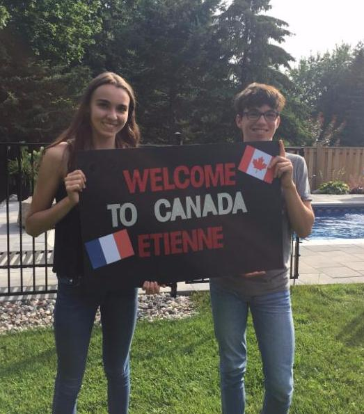 Female and male student holding a sign that says Welcome to Canada Etienne