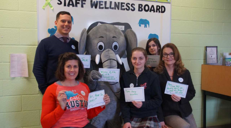 Female and male adults with female students and grey elephant sitting by school's Wellness bulletin board