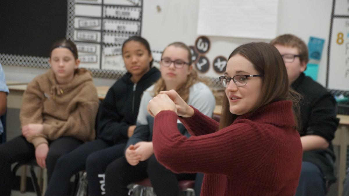 Female adult teaches students how to speak Ojibway.