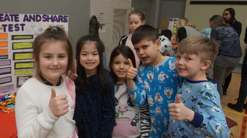 Female and male students give a thumbs up to the Lego Robotics projects.