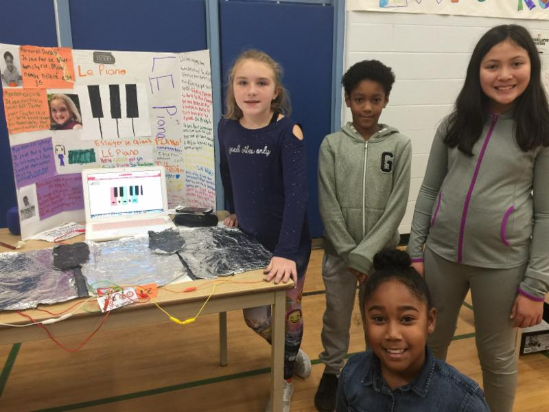 Student stand beside their robotics project