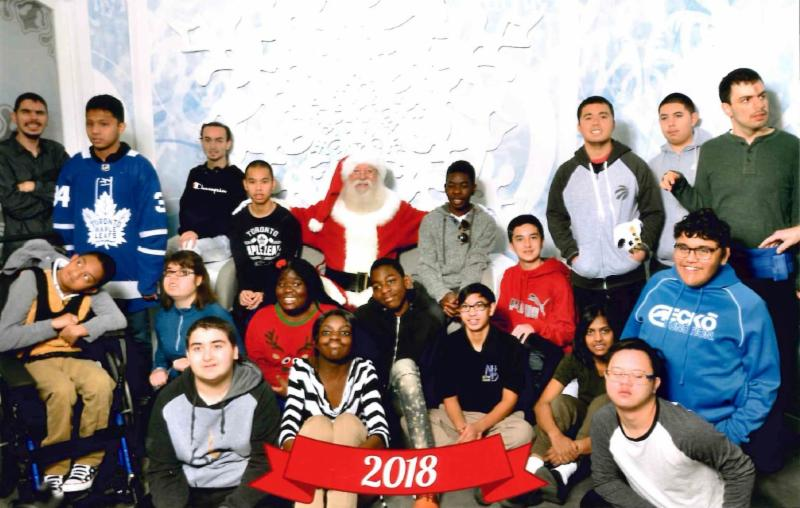 Male and female students have their picture taken with Santa at the mall.