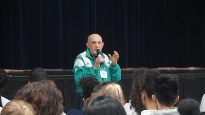 Male adult talking to students at an assembly