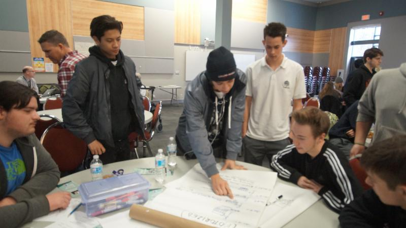 Male student sharing one groups ideas to a problem with another group