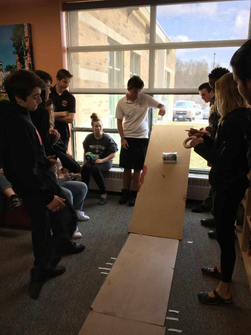 Students testing a vehicle they made on a cardboard ramp