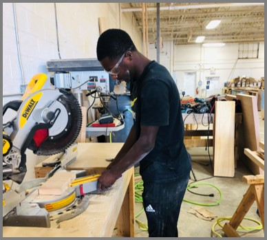 Male student working in a carpentry shop as part of his cooperative education placement