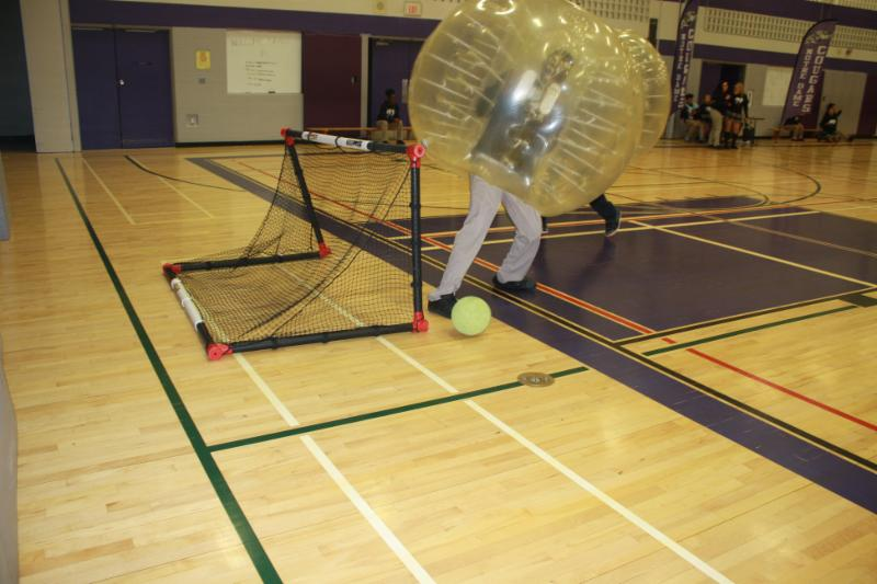 Student wearing a bubble costume and playing soccer