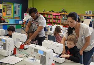 A male adult and female adult helping a female and male student on the sewing machines.