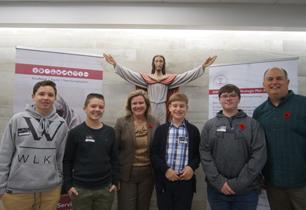 Director of Education and a male teacher stand with four male students in lobby with statue of Jesus behind them.