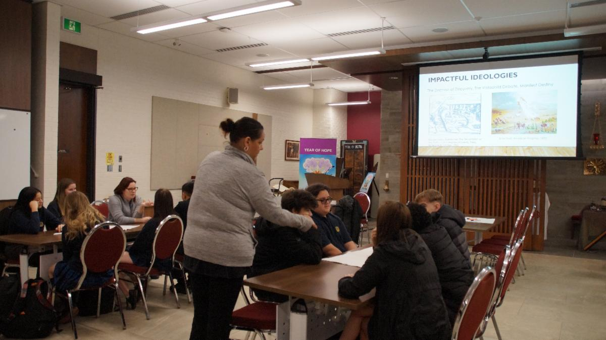 Female adult and member of the board's Indigenous Education Advisory Circle talking to students about Indigenous people.