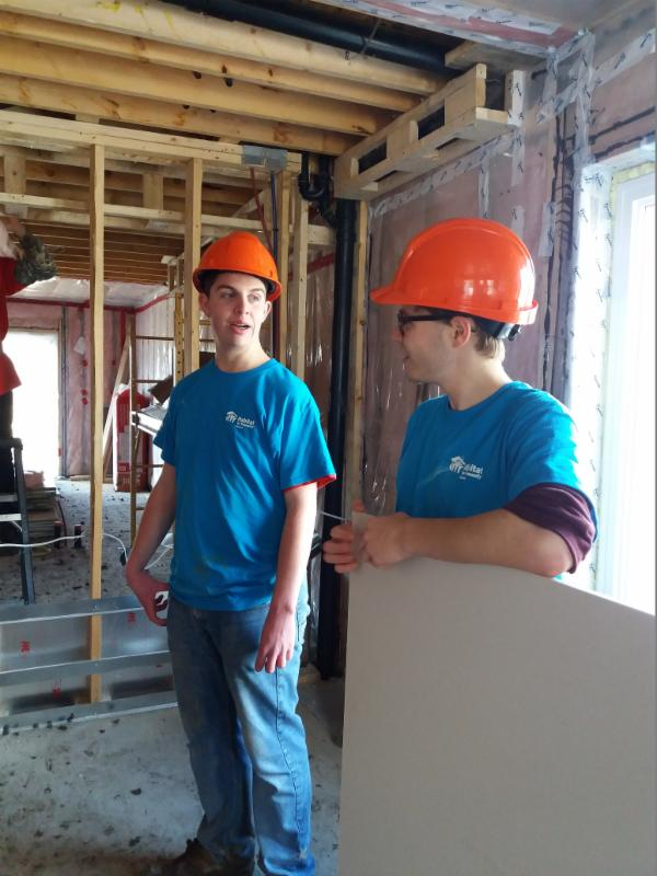 Male students help to drywall a home