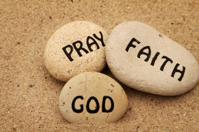 Three rocks in the sand saying God_ pray_ faith