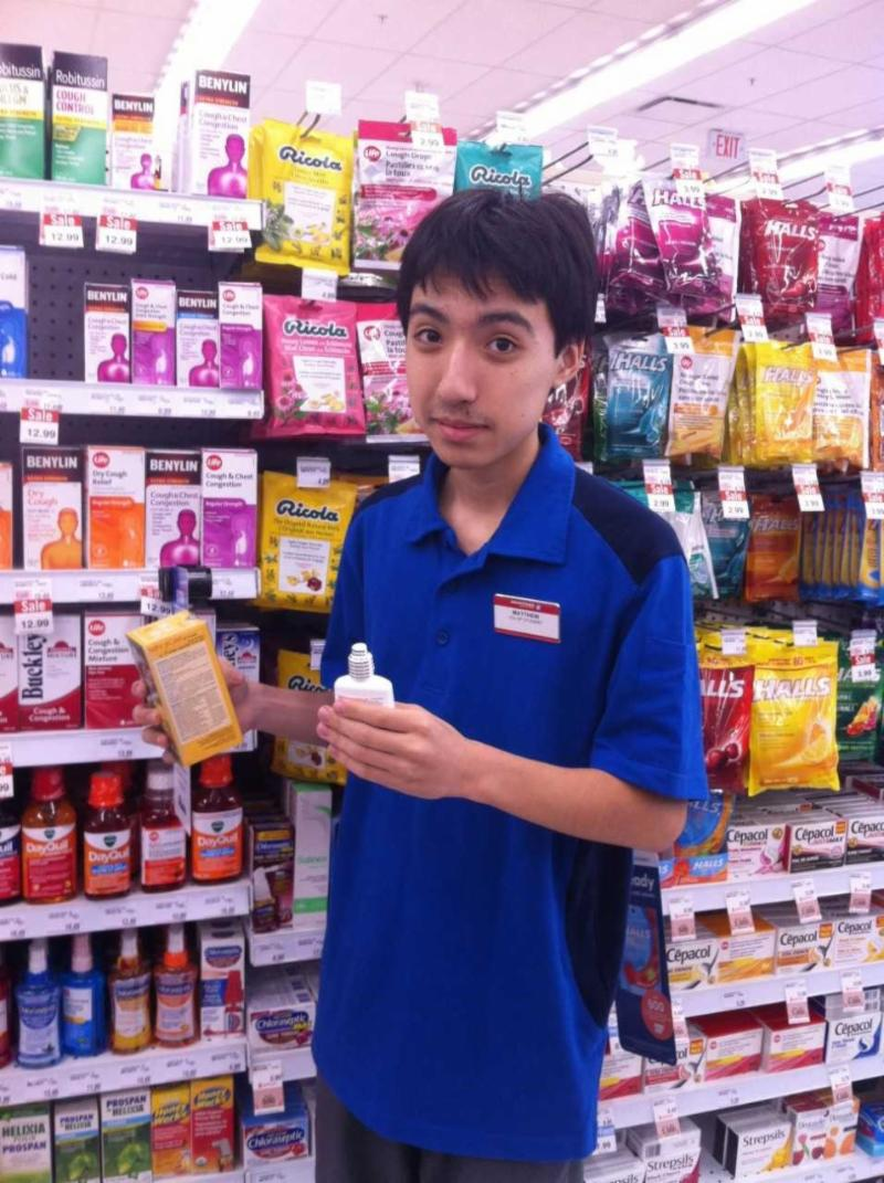 Male student filling shelves at a drug store.