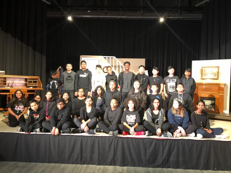 Male and female back crew students wearing black and smiling on stage
