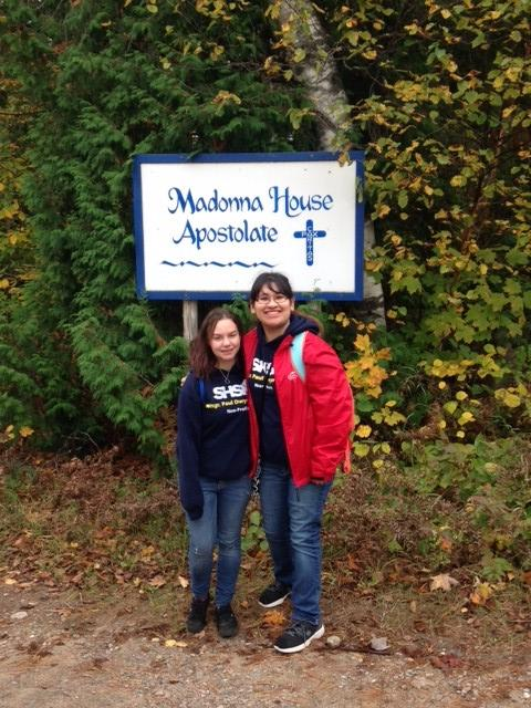 Two female student pose by Madama House sign