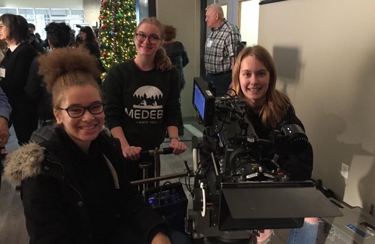 Three female students learning how to work a film industry camera.