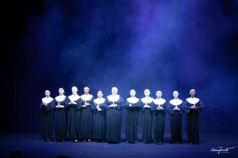 Eleven female students dressed as nuns singing on stage