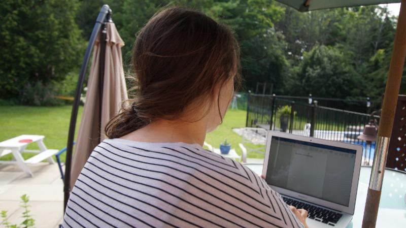 Female student working on her laptop outside in a backyard