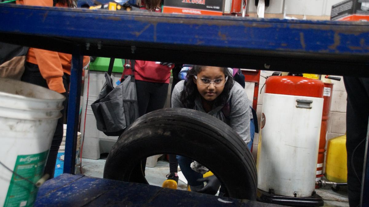 Female student working on a tire