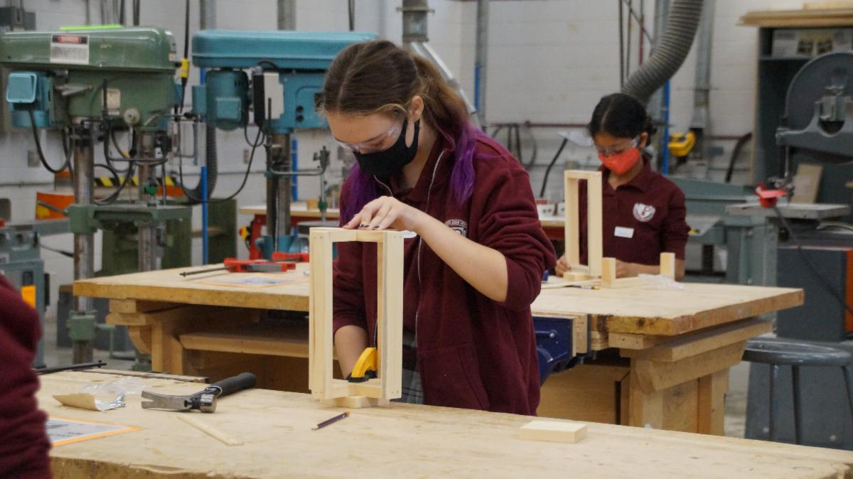 Female student clamping a wooden lantern to the table.