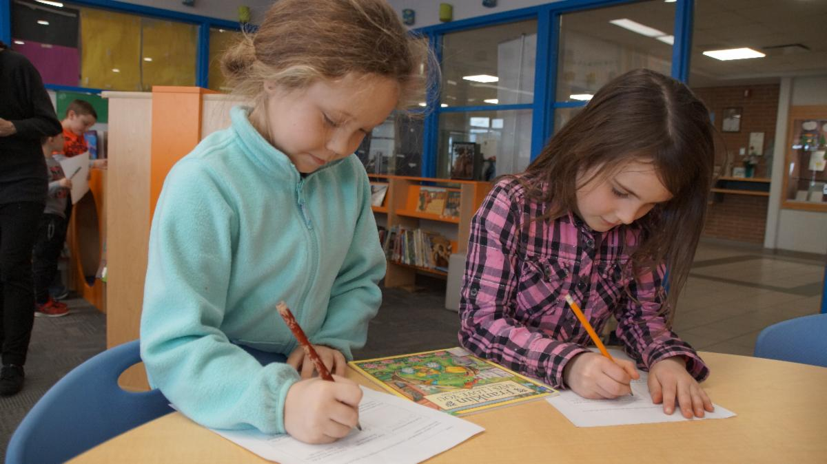 Two female students writing the name of an author down as part of their scavenger hunt