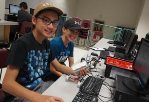 Two male students programming a robot in a computer lab