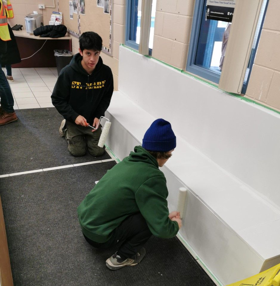 Two male students painting the bench white.
