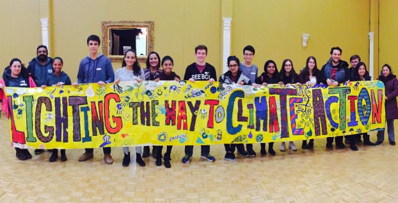 Students holding a banner that says Lighting the Way to Climate Action