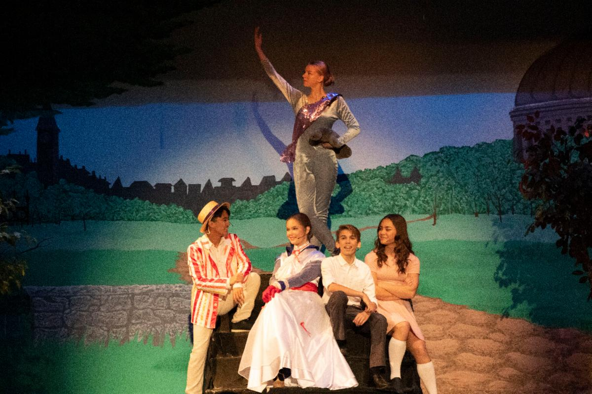 Male and female students on stage performing Mary Poppins