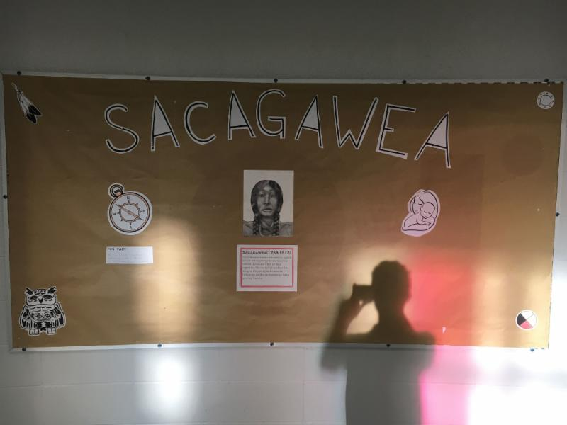 Male student taking a picture of the Indigenous Education bulletin board.
